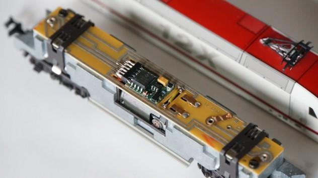 Schnittstellenstecker der BR 128 entfernt und Decoder fest angelötet. Ersatz der werkseitigen Spule durch eine Drahtbrücke (gelb)